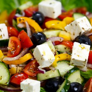 Fresh Close Up Vegetable Greek Salad with Feta cheese, black olives, cherry tomatoes, yellow pepper, red onion, cucumber. On wooden table