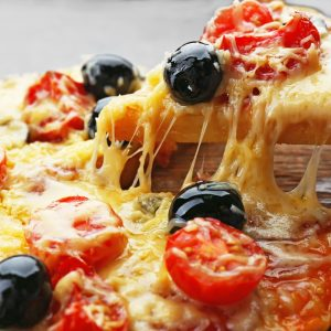 Sliced delicious pizza with olives on wooden plate, close up